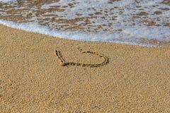 Сердце нарисованное на влажном пляже песка Часть сердца помыта прочь волной Символ начала или конец влюбленности Стоковая Фотография RF
