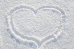 Сердце на белом, красивом снеге стоковые изображения rf