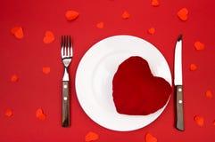 Сердце на плите для обедающего Романтичный вечер с сердцами на красной предпосылке стоковые фото