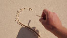 Сердце покрашенное с рукой на песке видеоматериал