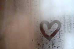 Сердце покрашено на misted стекле в зиме стоковое фото