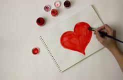 Сердце покрашено с красной краской на белом листе бумаги стоковое изображение rf