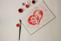 Сердце покрашено с красной краской на белом листе бумаги стоковые фотографии rf