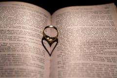 Сердце сделанное от тени кольца на книге Стоковые Фото