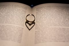 Сердце сделанное от тени кольца на книге Стоковые Изображения