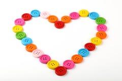 Сердце сформировало красочных шить кнопок на белизне Стоковое фото RF