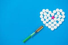 Сердце сформированное белых пилюлек и шприца Стоковое Изображение