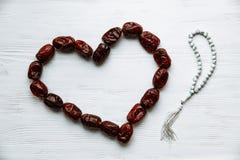Сердце сформированное датами и белым розарием для концепция сообщения Рамазан и пятницы стоковая фотография