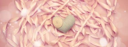 Сердце ткани знамени на предпосылке катушки декоративных лент сатинировки розового цвета Стоковое Изображение