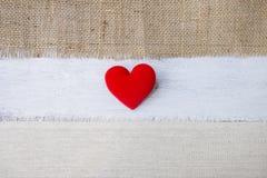 Сердце ткани красное на белой древесине с космосом на hessian и холст текстурируют предпосылку стоковое фото rf