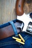 Серебристый револьвер nagant с патронами на старых голубых джинсах Стоковые Фото