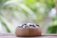 Серебряная монета в деревянном шаре помещена на деревянном поле с colorf Стоковое Фото