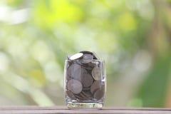 Серебряная монета в стекле помещена на деревянном поле с красочным bok Стоковые Фотографии RF