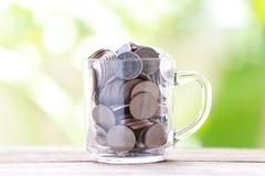 Серебряная монета в стекле помещена на деревянном поле с красочным bok Стоковая Фотография