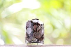 Серебряная монета в стекле помещена на деревянном поле с красочным bok Стоковое Изображение RF