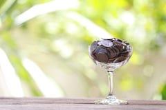 Серебряная монета в стекле помещена на деревянном поле с красочным bok Стоковое фото RF