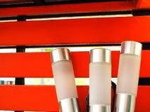 Серебряная пачка ручки лампы СИД белизны, красная деревянная стена Стоковые Фото