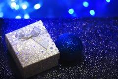 Серебряная подарочная коробка со смычком и сердца на темно-синей запачканной предпосылке стоковые фото