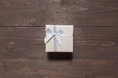 Серебряная подарочная коробка на деревянной предпосылке с пустым космосом Стоковое фото RF