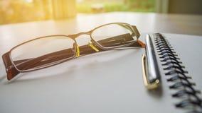 Серебряная ручка и открытый лежать спиральной тетради стоковая фотография