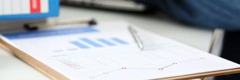 Серебряная ручка лежа на важном stats завертывает в бумагу закрепленный для того чтобы проложить Стоковая Фотография