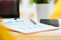 Серебряная ручка лежа на важном stats завертывает в бумагу закрепленный для того чтобы проложить Стоковое Изображение