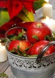 Серебряное ведро красных зрелых яблок среди свечей Стоковые Фото