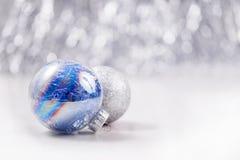 Серебряное и голубое рождество орнаментирует шарики на предпосылке bokeh яркого блеска с космосом для текста Xmas и счастливый Но Стоковые Фото