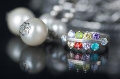 Серебряное кольцо с покрашенными диамантами и другие ювелирные изделия на черной предпосылке Стоковые Изображения RF