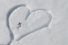 Серебряное распятие на сердце нарисованном в снеге Стоковая Фотография RF