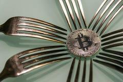 Серебряное bitcoin и серебряные вилки вокруг Стоковая Фотография