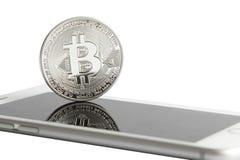 Серебряное bitcoin на smartphone Стоковое Изображение