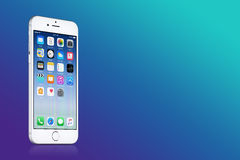 Серебряное iPhone 7 Яблока с iOS 10 на экране на голубой предпосылке градиента с космосом экземпляра Стоковое Изображение