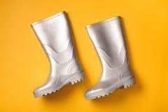 Серебряные ботинки дождя на желтом цвете Стоковые Фотографии RF