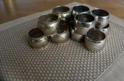 Серебряные держатели колец салфетки металла над золотой циновкой места цвета Подготавливайте для сервировки стола в событии, парт стоковое изображение