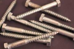 Серебряные ногти металла на темной предпосылке стоковое изображение