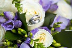 Серебряные обручальные кольца на букете свадьбы белых и фиолетовых цветков Стоковое фото RF