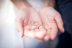 Серебряные обручальные кольца в руках женщины стоковая фотография rf