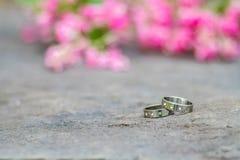 Серебряные обручальные кольца и розовые цветки на каменной предпосылке Стоковая Фотография