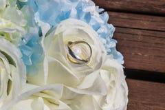Серебряные обручальные кольца на лепестках искусственного подняли стоковая фотография rf
