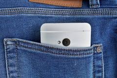 Серебряный алюминиевый smartphone помещенный на мужчине сшил голубое backpocket ` s демикотона Стоковые Изображения