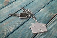 Серебряный домашний ключ с значком на деревянном столе Стоковая Фотография