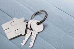 Серебряный домашний ключ с значком на деревянном столе Стоковые Изображения RF