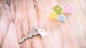 Серебряный ключ с Breloque в форме дома на Vhain с некоторым миниатюрным символом домов на стороне в других цветах дальше Стоковая Фотография RF