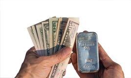 Серебряный миллиард 1 кило и долларовая банкнота в руках изолированных на белизне стоковое фото rf