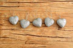 6 серебряных сердец изолированных против деревянной предпосылки Стоковая Фотография