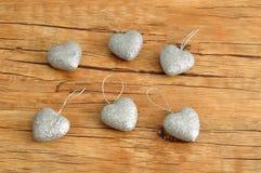 6 серебряных сердец изолированных против деревянной предпосылки Стоковое Изображение RF