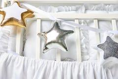 Серебр, золото и белая звезда сформировали подушки на белой кроватке младенца Стоковое Изображение RF