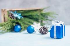 Серебр и голубой подарок игрушки, игрушки рождества разливают из деревянной коробки с зелеными ветвями дерева Стоковое Изображение RF