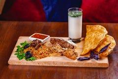 середина кухни восточная Pasties, kebabs, pilaf, ayran на деревянной разделочной доске стоковое фото